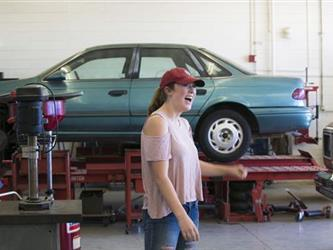 girl in baseball cap with car on lift