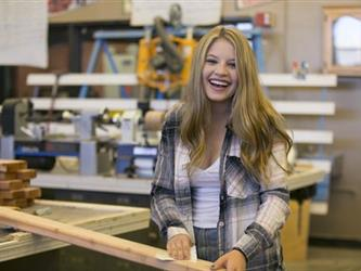 girl in shop class with lumber